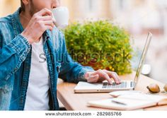 Starting his day with cup of coffee. Cropped image of young man drinking coffee and working on laptop while sitting at sidewalk cafe - stock photo