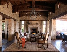 Other designers could have looked at the living room walls, made of Santa Barbara sandstone, and thought castle, grand. Michael S. Smith thought primitive, pure. Sofas are slipcovered in Avigdor's Chan in Cream; the simple lines echo the shape of the 17th-century Chinese coffee table from Charles Jacobsen.