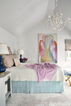 A painting by Sara Robichaud influenced the master bedroom colors. Julie Neill Design's Plastered chandelier and a coverlet from West Elm soften the dynamic bed skirt in Peter Fasano's Sarpa. The walls are painted in Benjamin Moore's Balboa Mist.