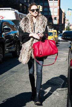 Olivia Palermo wears a sheer black blouse, fur stole, skinny jeans, moto boots, red Louis Vuitton duffle bag, and round sunglasses