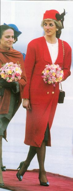 Princess Diana arriving at Orly Airport, November 1988. Diana is wearing Karl Lagerfeld for Chanel: A red wool double-breasted coat over a white silk blouse and skirt, along with a hat with a long feather plume, and iconic Chanel shoulder bag. The previous pin features a close-up of her hat.