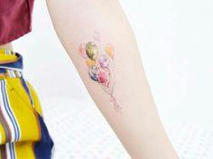 Small watercolor balloons tattoo