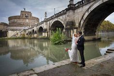 Bride and groom down underneath the bridge of Saint Angel Castle in Rome. Photo by Andrea Matone #wedding photographer.