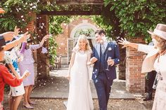 Bride & Groom Confetti Portrait - Image by Lemonade Pictures - A Lace Raimon Bundo Wedding Dress & L.K.Bennet Shoes for a traditional English country wedding with Beaded Virgos Lounge ASOS Bridesmaid Dresses & Navy REISS Groomsmen suits.