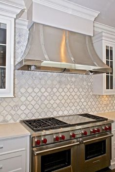 Beautiful kitchen features a stainless steel French kitchen hood stands over a white Moroccan tiled backsplash as well as a Wolf dual range.