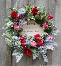 """""""Love"""" Rose Garden Wreath. Lush flocked leaves set the background for a beautiful array of roses, Queen Anne's Lace and dainty wildflowers gracing the edge of a 14"""" grapevine frame. The wreath's cente"""