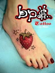 Strawberry and star tattoos on foot