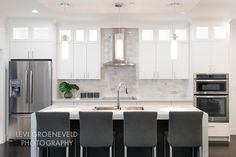 """The kitchen features a beautiful 3"""" thick white quartz waterfall island countertop. We chose white carrara marble subway tile for the backsplash and added custom charcoal bar stools to add contrast."""