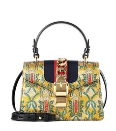 Gucci - Sylvie Mini brocade shoulder bag - Gucci's Sylvie mini bag comes in sheeny brocade fabric for notice-me shimmer. Glossy golden hardware adds luxe elevation, while the label's signature web stripe brings recognition. Carry yours by the ladylike top handle or attach the shoulder strap to go hands-free. seen @ www.mytheresa.com