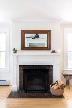A rectangular mirror above a traditional fireplace feels fresh because of the minimal accessories.
