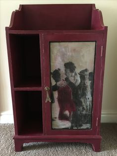 Cabinet, painted with Annie Sloan Chalk Paint Burgundy, with image transfer of Robert Doisneau's 'Le Baiser de l'Hotel de Ville, Paris, 1950' (The Kiss). Lightly distressed and sealed with clear wax for protection. With Anthropologie Eiffel Tower door pull.