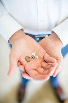groom holding cuffli