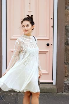 Amy Spencer is wearing a white lace sleeve dress from Free People