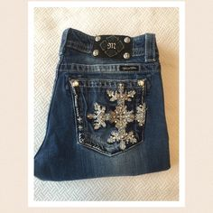 """Miss Me jeans. Inseam 33"""" Snowflake design Silver sparkle snowflake pocket design. Dark wash slightly distressed denim, boot cut with heavy stitching, snowflake design and embellished with studded sparkling accents. Very gently pre-lived with only minimal signs of wear on front pockets. 98% cotton 2% elastane Excellent condition. Waist 32"""" Front rise 8"""" Back rise 13"""" Half hip 19.5 Full hip 20.5"""" Miss Me Jeans Boot Cut"""
