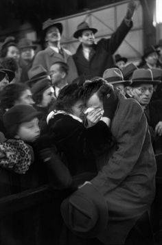 The arrival of a boat carrying refugees from Europe reunites a mother and son who had been separated throughout the war. By Henri-Cartier Bresson, 1946.