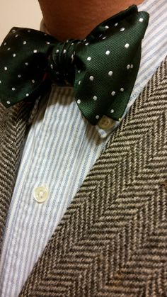Grey herringbone tweed jacket, white shirt with light blue dress stripes, green bow tie with white polka dots