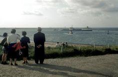 Tussen de pieren van [IJmuiden] vaart de Elmar. Dagjesmensen kijken toe in de namiddagzon in de wind [Nederland] 16 augustus 1959.
