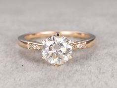 Moissanite Engagement ring,14K&18K Rose/Yellow/White Gold Available. Every Jewelry in my store needs making to order. The Engagement ring features a 6.5mm Round Cut Charles & Colvard Moissanite,diamond go half around the band. [Item details] Engagement Ring: Solid 14K Yellow Gold(Can be made in white/yellow/rose gold) band width(bottom):approx 1.38mm band width(top):approx 1.65mm bottom height:approx 1.06mm Size 5#(Ring can be resized) 6.5mm Round cut 1ctw Cha...