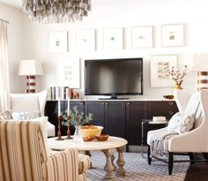 Living room, big screen TV, dark wood cabinets, prints, grey printed carpet, striped chair