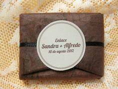 Jabón artesanal envuelto en papel de plátano y decorado con una cinta de raso negro. Detalle de boda.
