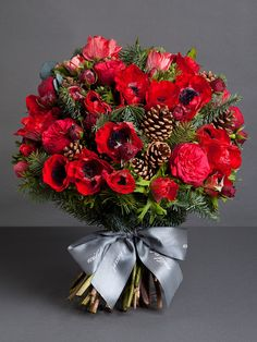 CLASSIC ANEMONE BOUQUET A rich mix of red anemones, red piano roses, pine and pine cones makes this bouquet beautifully textured, abundant and the perfect arrangement for a festive centrepiece. http://shop.wildatheart.com/collections/christmas-bouquets/products/classic-anemones-bouquet