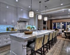 """Kitchen. Kitchen Ideas. White Coastal Kitchen Design. Pendant Lighting are from Visual Comfort. Ikat fabric on the back of the stool is the """"Kelly Wearstler Bengal Bazaar in Murshroom/Straw GWF-2811-614 for Lee Jofa"""".#Kitchen #CoastalKitchen #KitchenDesign"""