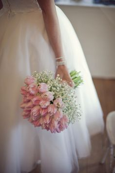 A beautiful hand tied bouquet of pale pink tulips and ivory gypsophila.