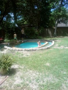 "i designed this homemade pool and with help building it and many hours of work...a swimming pond. it had a liner,a dock and ladder and no chemicals. the ""moat"" area around the pool was filled with gravel that would act as a natural filter when filled with plants. this was taken pre plants. thats Helaina and Sadie."