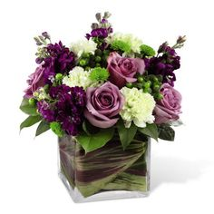 A compact arrangement of green and purple flowers designed in a leaf lined square vase.