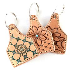 Hand tooled leather cow tag key chain- Made out of Herman Oak leather and machine sewn with a backing. These cute western charms make a perfect gift! Keychains are 2 inches wide and 3 inches tall Leather Accessories, Leather Jewelry, Leather Craft, Cactus Keychain, Leather Tooling Patterns, Diy Leather Projects, Ear Tag, Leather Stamps, Tooled Leather