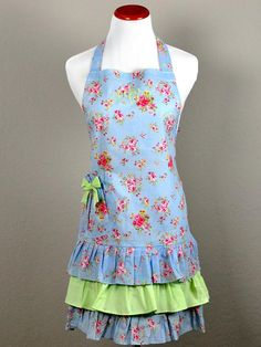 """Vintage Inspired Romantic Spring Hostess Apron What woman wouldn't want to serve their guests in this cute romantic hostess apron? This spring inspired hostess apron is made with light blue floral fabric and lime green accents. There is also a small side pocket in the front that is super functional.  The apron is made of 100% cotton and measures 10"""" from neck to waist, 20"""" from front waist to bottom, 22"""" across the waistband + 2 ties on both sides.  Very lovely and perfect for a ladies l..."""