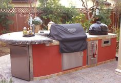 Smoker, Kegerator, Refrigerator,   The only thing this island is missing is the kitchen sink. Counter top is a multi color slate with small mosaic tiles around the edge of the seated counter section. The sides are stucco and painted.