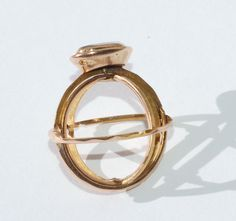 A gold ring circa 1780, of interlocking hinged hoops which unfold into a miniature armillary sphere, with a crystal covered bezel containing a lock of hair. The interlocking hoops are concealed when the ring is closed. Armillary spheres were used to show the movement of the planets around the sun, but the ring would not have been usable as such and illustrates the fascination with science common in the 18th century.