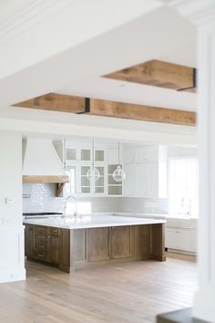 An expansive coffee stained kitchen island is accented with polished nickel hardware and a white marble countertop with a sink and a polished nickel gooseneck faucet lit by three glass pendants.
