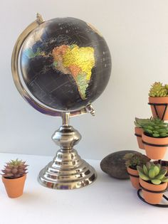 This mid sized globe is striking. It has a polished silver base that is graduated. The sphere is black with continents and countries colored in