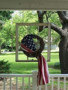 hang an old widow..wrap flag around wreath..secure wreath to window..great Memorial Day or 4th display..simple and one of a kind idea...( I would break the glass out of the window and just use the frame..much lighter in weight and less fear of falling)