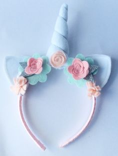 Your child will want to wear this ice cream pastel inspired unicorn headband everyday, it is so much fun! The ears and horn are both handmade from white acrylic felt, and the horn has polyester stuffing so it will stand up straight. The ears and horn are surrounded by pretty felt flowers in every pastel shades. The plastic headband is covered in pink grosgrain ribbon making it very comfortable to wear.  Inspired by British fairy tales, the headband is a great accessory for a birthday party…