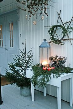 Traditional Christmas tree in a vintage pottery pot and greenery and a vintage metal lantern with creme colored candles...