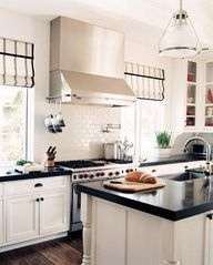 Luscious kitchens - mylusciouslife.com - White & black contemporary kitchen design with white kitchen cabinets, black counter tops, white subway tiles backsplash, pot filler, silk white gray striped roman shades, glass-front cabinets, rustic wood floors