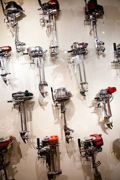 Wall of polished antique outboard motors in Daniels Antiques Las Olas location