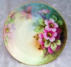 "Attractive Vintage Bavaria 1900's Hand Painted ""Wild Pink Roses"" on stem and leaf against a background of heavy shadow leafing and background colors of light creme yellow, light several shades of creme green, creme brown, brown and a light creme blue steel. A heavy gilded gold outer rim adds to its beauty. 9-1/4"" Plate by the Early Chicago Artist, ""M. Perl"""