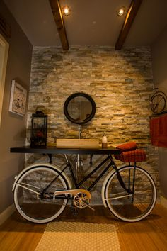 vintage bicycle bathroom, with a bike tire as a mirror, basket that hold are hand towel and a bamboo sink and floor.inspired by pintrest.