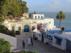 Cobblestone streets connecting whitewashed houses with blue shutters and doors are trademarks of Sidi Bou Said near Tunis, Tunisia. Trendy cafes and art galleries flourish here. Sidi Bou Said, Blue Shutters, Carthage, Small Towns, Travel Inspiration, Art Gallery, Mansions, Architecture, Flourish