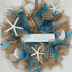 "22"" in Diameter Burlap and Teal Deco Mesh wreath accented with several types of ribbon (Teal, Tan, and White) along with three Starfish and 3 Sand-dollars. sign is optional."