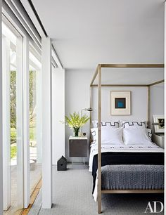 A bright bedroom featuring a silkscreen by Josef Albers, a Room & Board four-poster bed | archdigest.com