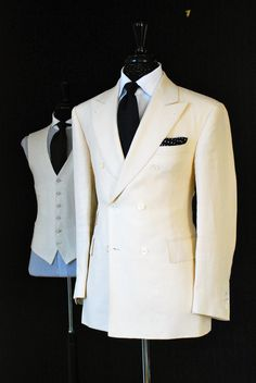 Double-breast white blazer, black necktie, black and white-dotted pocket-square. In the background, a white vest, with a black necktie, and a white under-shirt.