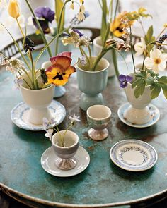 For an Easter centerpiece, arrange several eggcups of spring flowers on a tray.