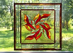Measures approximately 25.75w x 25.75h.    This square panel has a sunburst or floral design at its center focal point. It is a bevel cluster