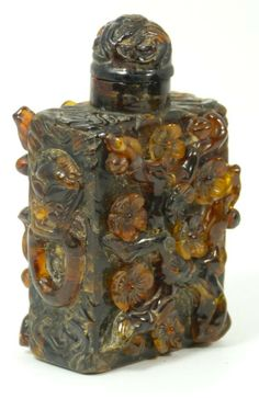Antique Chinese hand carved amber snuff bottles with relief floral design throughout. Sides have raised foo dog masks. 19th century