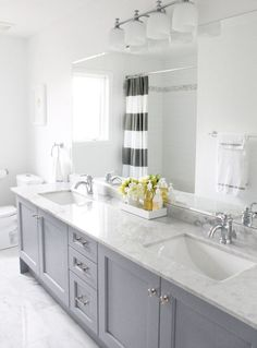 Love the light gray vanity + striped curtain